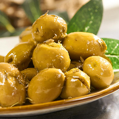 Grüne Oliven mit Kräutern in Olivenöl